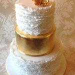 Gold leaf wedding cake with white ruffles